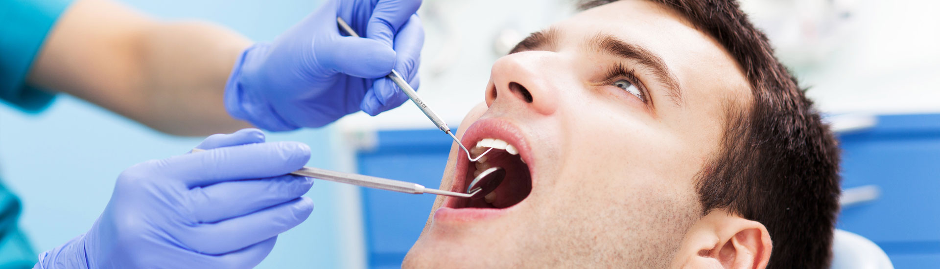 A man is having his teeth examined at dentists
