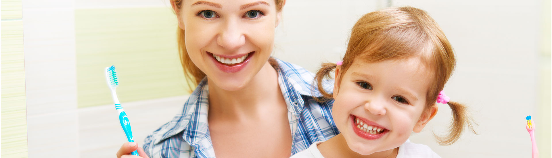 Mother and daughter smiling while holding toothbrushes